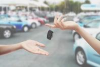 Chiavi consegnate in mano sfondo parcheggio auto