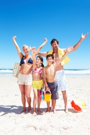 Family throwing arms up with beach gear