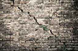 Cracked brick wall - Deep crack in a brick wall - toned image